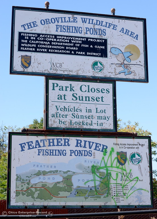 . A sign says the park closes at sunset and vehicles in lot may be locked in while another lower sign has been vandalized at Riverbend Park in Oroville, Calif. Friday Sept. 22, 2017. (Bill Husa -- Enterprise-Record)