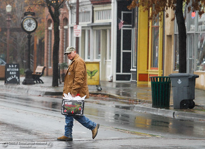 A man crosses Montgomery Street with a Christmas present bought from a store downtown December 8, 2016 in Oroville, California. (Emily Bertolino -- Mercury Register)