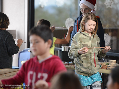 Lilli Pierson, 11, looks down at the candle she is making during Frontier Christmas Saturday December 2, 2017 at the at Lake Oroville Visitor Center in Oroville, California. (Emily Bertolino -- Mercury Register)