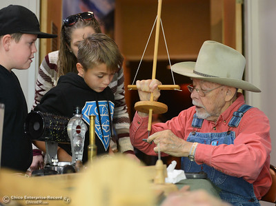 Miles Walbrecht, right demonstrates how to use an old fashion drill as Francisco Pina, 10, and Cody Alexander, 10, left, watch during Frontier Christmas Saturday December 2, 2017 at the at Lake Oroville Visitor Center in Oroville, California. (Emily Bertolino -- Mercury Register)