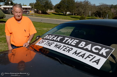 """Don Blake stands beside his car, posted with Water Mafia signs as he stages a protest outside of the DWR Offices on Glen Drive in Oroville, Calif. Monday Feb. 12, 2018. Blake is seeking the name of the DWR Executive responsible for """"The decision to cut back water flows down the main spillway from 65,000 to 55,000 cfs on the evening of February 10th 2017."""" Blake claims that Pat Whitlock knows this information and refuses to give up a name. (Bill Husa -- Enterprise-Record)"""
