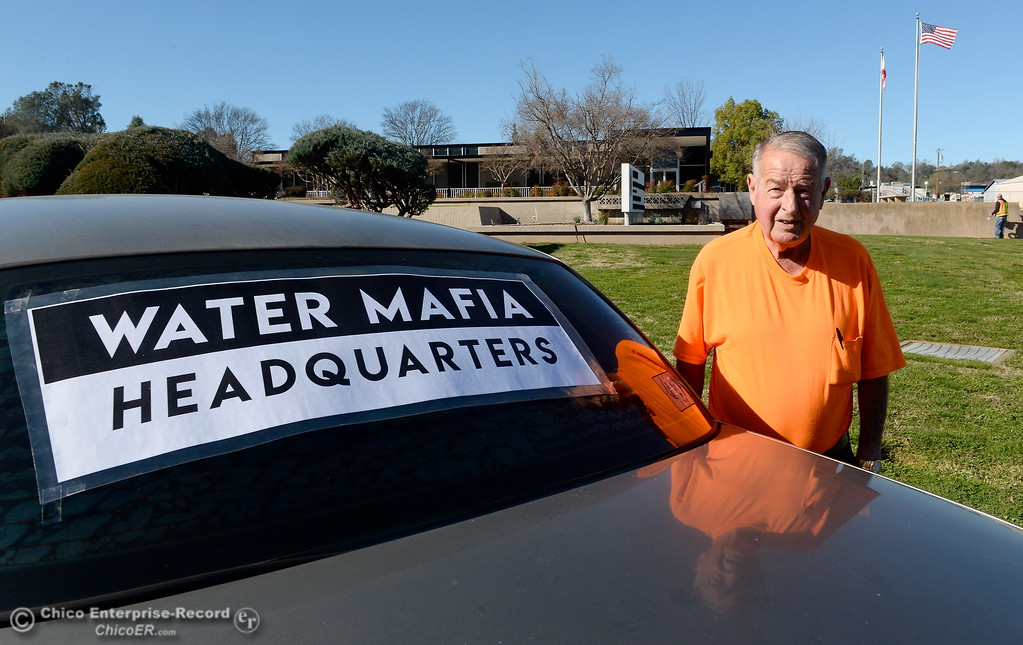 ". Don Blake stands beside his car, posted with Water Mafia signs as he stages a protest outside of the DWR Offices on Glen Drive in Oroville, Calif. Monday Feb. 12, 2018. Blake is seeking the name of the DWR Executive responsible for ""The decision to cut back water flows down the main spillway from 65,000 to 55,000 cfs on the evening of February 10th 2017.\"" Blake claims that Pat Whitlock knows this information and refuses to give up a name. (Bill Husa -- Enterprise-Record)"