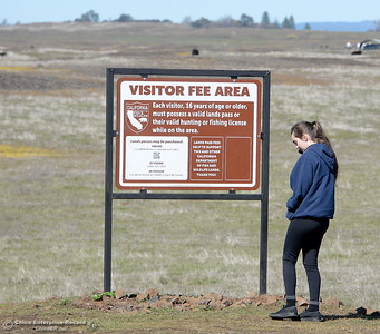 Holly Shafer of Davis calls the phone number on the sign as she gets ready to enjoy a stroll through the wildflowers  just beginning to bloom on Table Mountain Monday March 5, 2018. Hikers 16-years or older are now required to have a Lands Pass or valid hunting or fishing license. (Bill Husa -- Enterprise-Record)