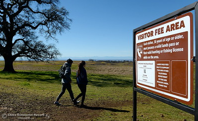Cliff Chao left and Holly Shafer of Davis walk past the visitor fee sign as they head out on a stroll through the wildflowers just beginning to bloom on Table Mountain Monday March 5, 2018. Hikers 16-years or older are now required to have a Lands Pass or valid hunting or fishing license. (Bill Husa -- Enterprise-Record)