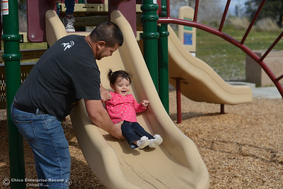 Jacob Duran helps his daughter, Lia, down a slide in Riverbend park, Thursday, March 8, 2018, in Oroville, California. (Carin Dorghalli -- Enterprise-Record)