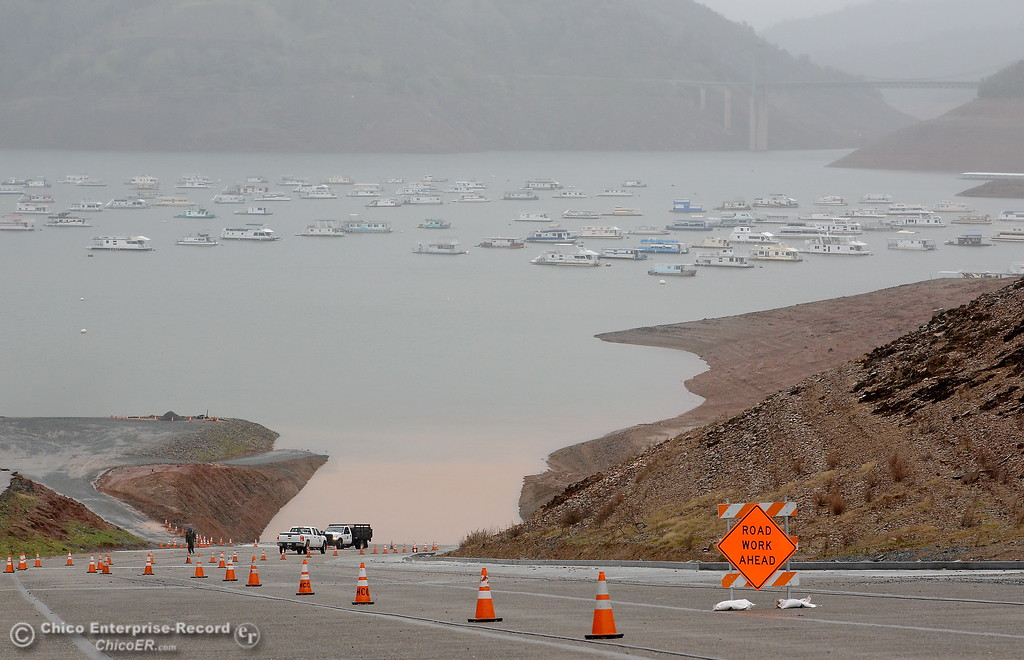 . California State Parks employees drag a cable up the hill as they adjust for a rising Lake Oroville as rain continues in Oroville, Calif. Thurs. March 15, 2018. (Bill Husa -- Enterprise-Record)
