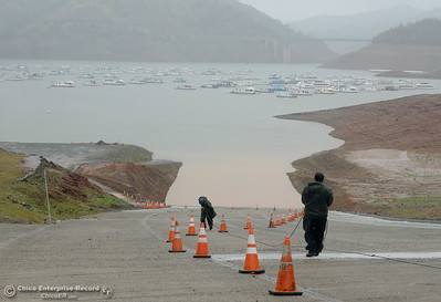 California State Parks employees drag a cable up the hill as they adjust for a rising Lake Oroville as rain continues in Oroville, Calif. Thurs. March 15, 2018. (Bill Husa -- Enterprise-Record)