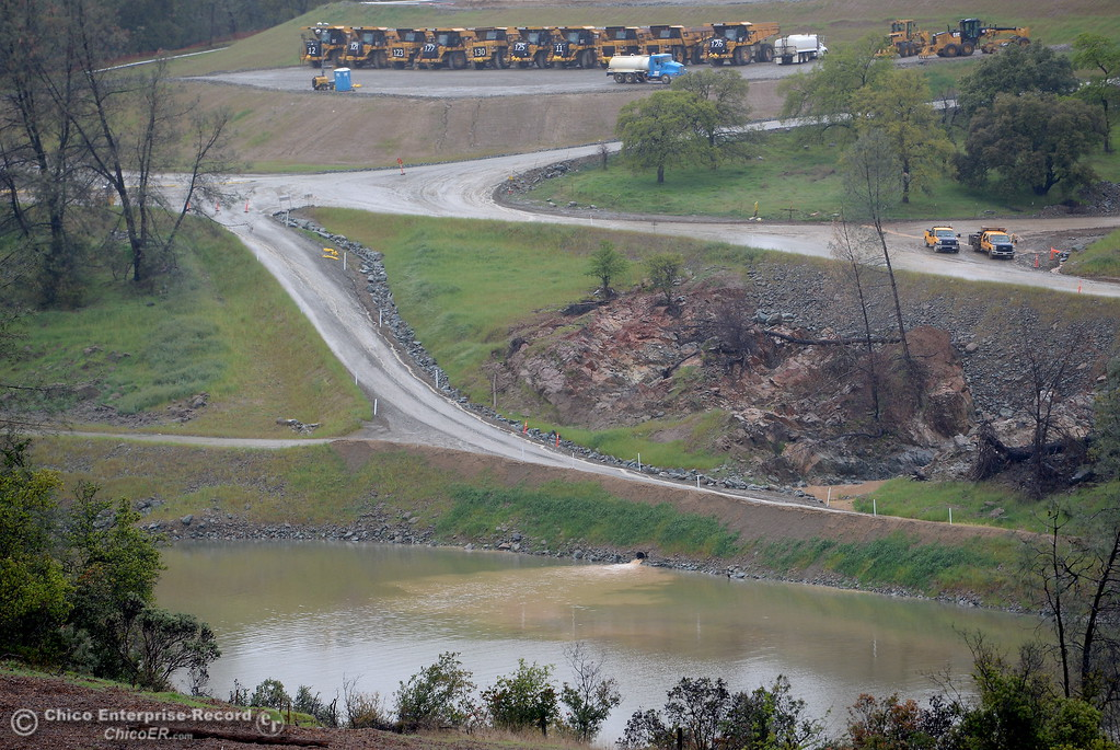 . Muddy water can be seen draining into the river below roads and trucks near the spillway as rain pours around Butte County Calif. Wednesday March 21, 2018.  (Bill Husa -- Enterprise-Record)