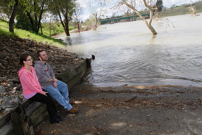 Fayth Davis and Kyle Smith sit next to the Feather Rivers edge since the river's high level blocks off the bike path March 21, 2017 Bedrock Park in Oroville,California. (Emily Bertolino -- Enterprise-Record)