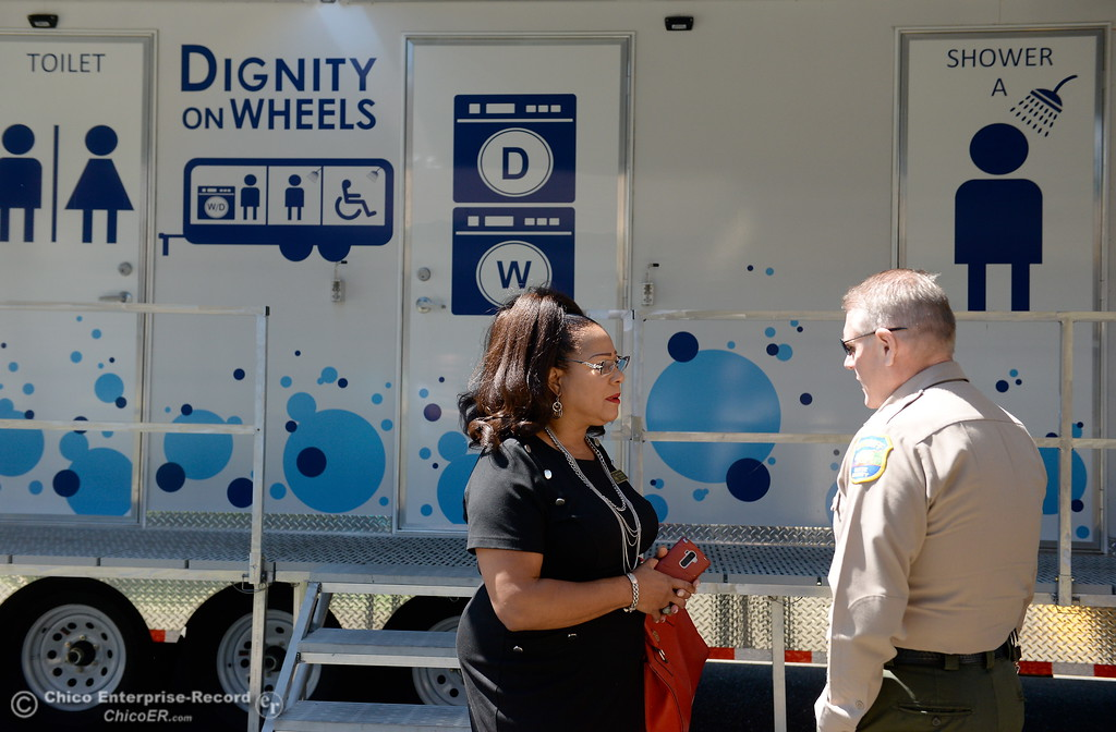 . Oroville Vice Mayor Janet Goodson talks with Butte County Sheriff Kory Honea in front of a Dignity on Wheels trailer parked at the Southside Community Center where the local nonprofit is presenting plans for a homeless care unit that includes showers, toilet and laundry facility Wednesday May 9, 2018. (Bill Husa -- Enterprise-Record)