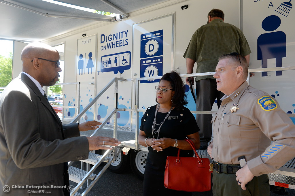 . Pastor Paul Bains with project WeHOPE out of Palo Alto at left talks with Oroville Vice Mayor Janet Goodson and Butte County Sheriff Kory Honea beside a trailer parked at the Southside Community Center where the local nonprofit is presenting plans for a homeless care unit that includes showers, toilet and laundry facility Wednesday May 9, 2018. (Bill Husa -- Enterprise-Record)
