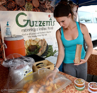 Stephani Bricker serves up some Samosas from the Guzzettis booth during the Farmers Market in Oroville, Calif. Wed. June 7, 2017. (Bill Husa -- Enterprise-Record)