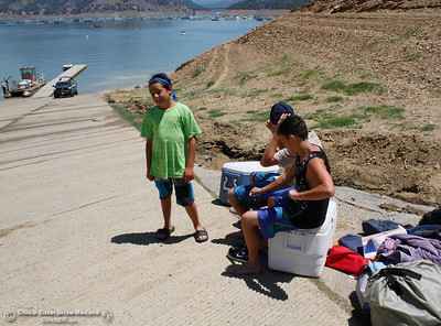 Kayne Thomson, left, smiles as Cyrus Moezzo and Jaxden Thomson wait with their camping gear as the rest of the family works to get the boat loaded after a three day camping trip on the lake Tuesday June 20, 2017 at Bidwell Canyon Marina  in Oroville, California. (Emily Bertolino -- Mercury Register)