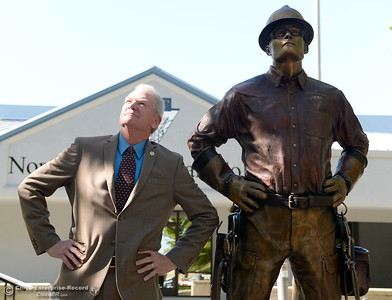 Butte County District Attorney Mike Ramsey tries to mimic the pose of the new statue during the unveiling of The Bronze Lineman statue at the Northwest Lineman College in Oroville, Calif. Wed. July 12, 2017. (Bill Husa -- Enterprise-Record)