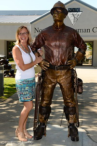 Mayor Linda Dahlmeier smiles beside the new bronze statue during the unveiling of The Bronze Lineman statue at the Northwest Lineman College in Oroville, Calif. Wed. July 12, 2017. (Bill Husa -- Enterprise-Record)