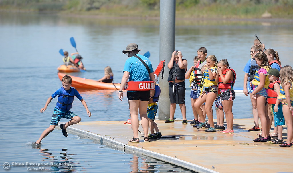 . A boy jumps off of the dock to act as a victim as Instructor Ashley Freitas teaches participants at the Forebay Aquatic Center how to perform dock rescues at the Forebay in Oroville, Calif. Wed. July 26, 2017. (Bill Husa -- Enterprise-Record)
