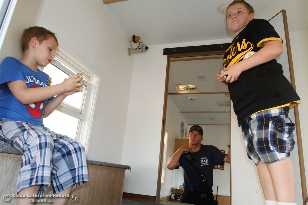 . Oroville Fire Department firefighter Jordan Thompson (center) talks with brothers Shane, 7, and Sam Knipp, 10, about what to do in case of a fire during the National Night Out Tuesday August 1, 2017 at the Municipal Auditorium in Oroville, California. (Emily Bertolino -- Enterprise- Record)