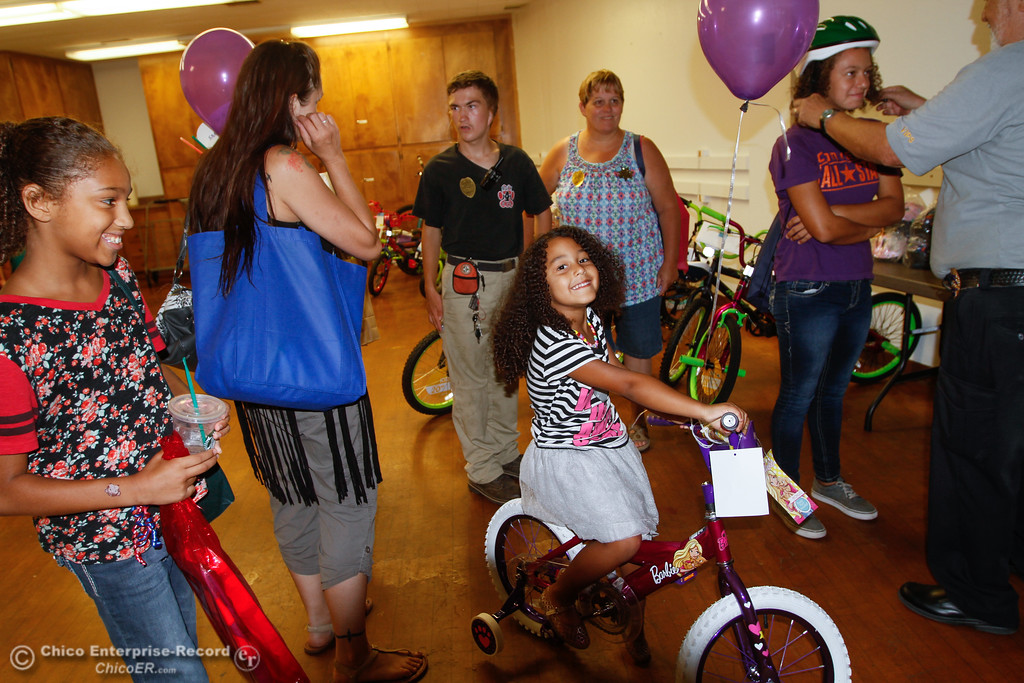 . Zuri Bochantin, 4, smiles on her new bike as her sister Lataya (right), 14, gets her helmet fitted and other sister Kashsha (left) looks on during the annual National Night Out Tuesday August 1, 2017 at the Municipal Auditorium in Oroville, California. (Emily Bertolino -- Enterprise- Record)