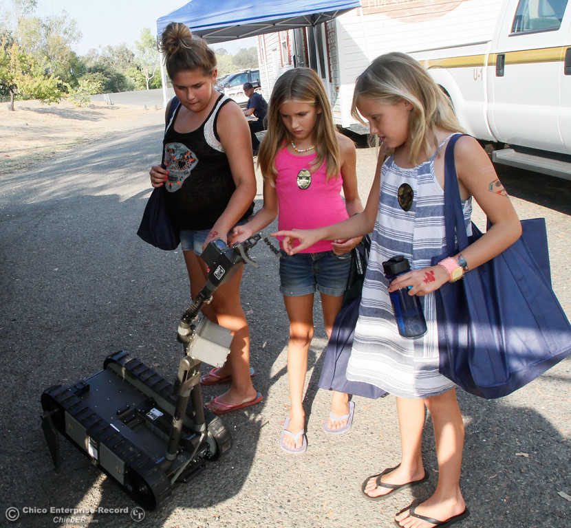 . Sisters Jewel Mason, 12, Maddie, 9, and Maya, 10, (left to right) interact with one of the new Butte County Inter-Agency Bomb Squad\'s robots during the annual National Night Out Tuesday August 1, 2017 at the Municipal Auditorium in Oroville, California. (Emily Bertolino -- Enterprise- Record)