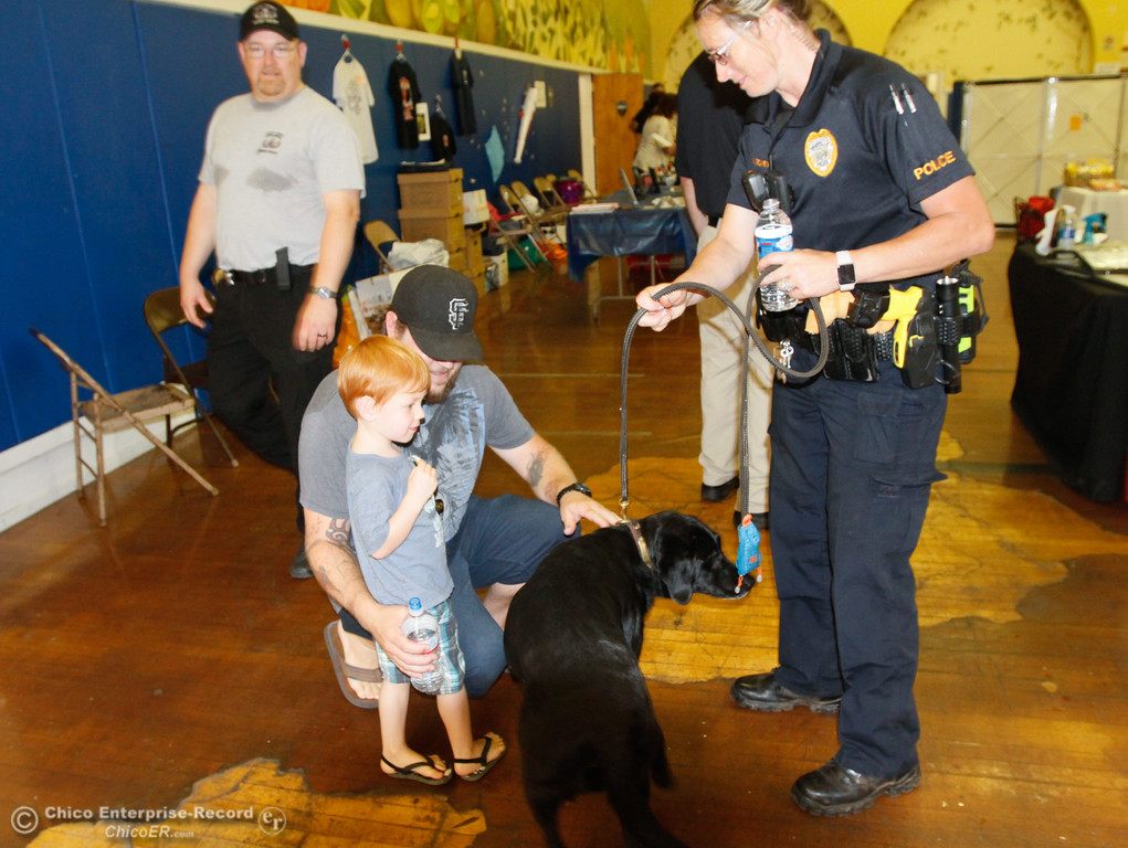 . Conner Fackrell, 3, and Karl Fackrell pet Roxy a fire K-9 dog as Marnie Gedney, Oroville police officer and Oroville firefighter looks on during the annual National Night Out Tuesday August 1, 2017 at the Municipal Auditorium in Oroville, California. (Emily Bertolino -- Enterprise- Record)
