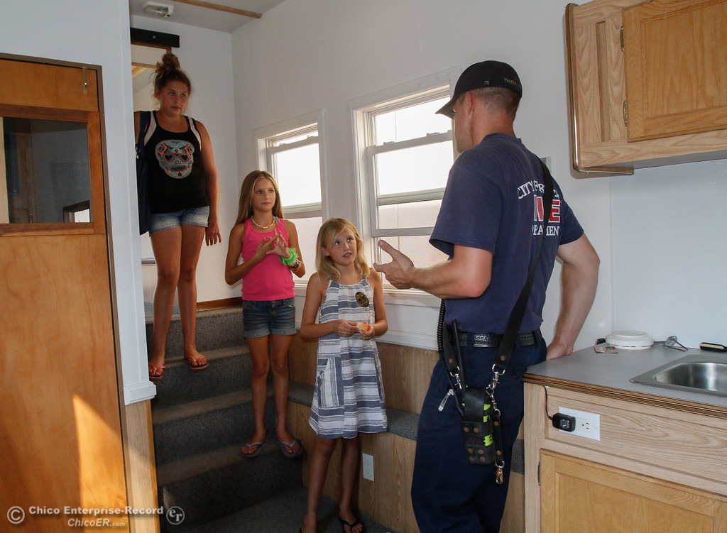 . Oroville Fire Department firefighter Jordan Thompson talks with sisters Jewel, 12, Maddie, 9, and Maya Mason, 10, (left to right) about what to do in case of a fire in the Fire Safety House during the National Night Out Tuesday August 1, 2017 at the Municipal Auditorium in Oroville, California. (Emily Bertolino -- Enterprise- Record)