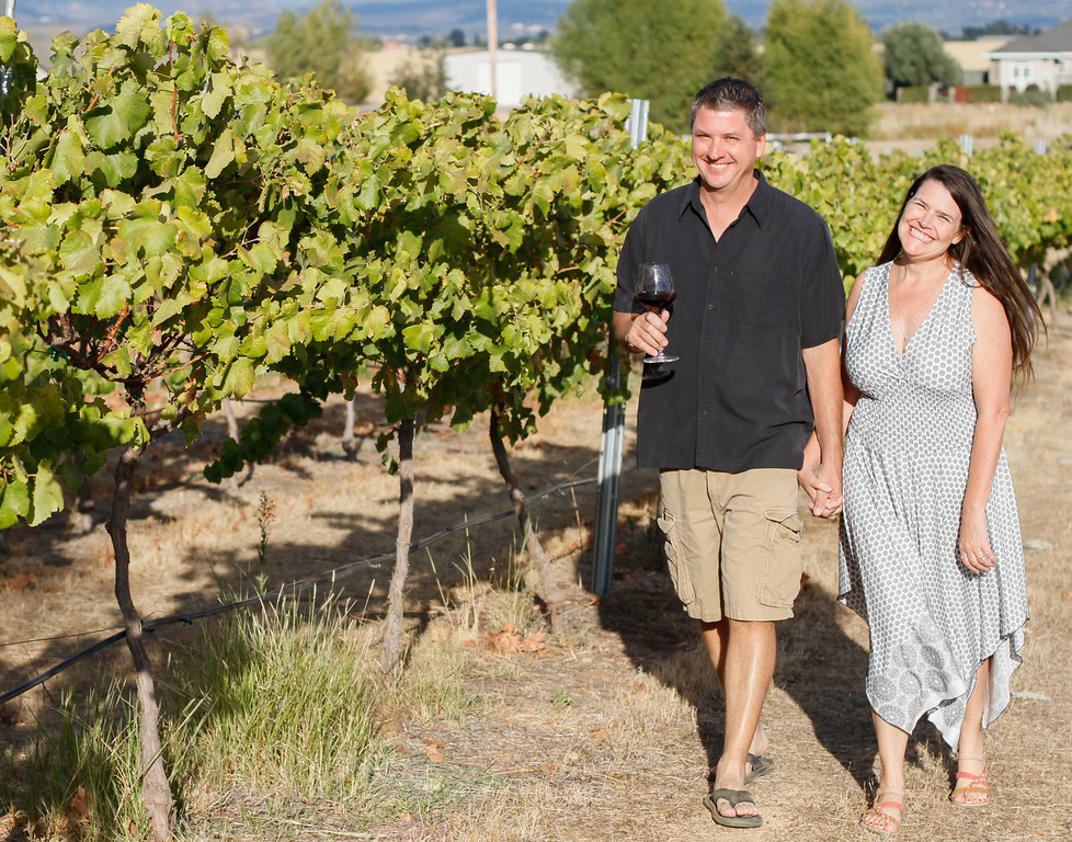 . Susan and Shawn Smith take a stroll through their grape vines at Live Vine Wines September 22, 2017 in Oroville, California. (Emily Bertolino -- Mercury Register)
