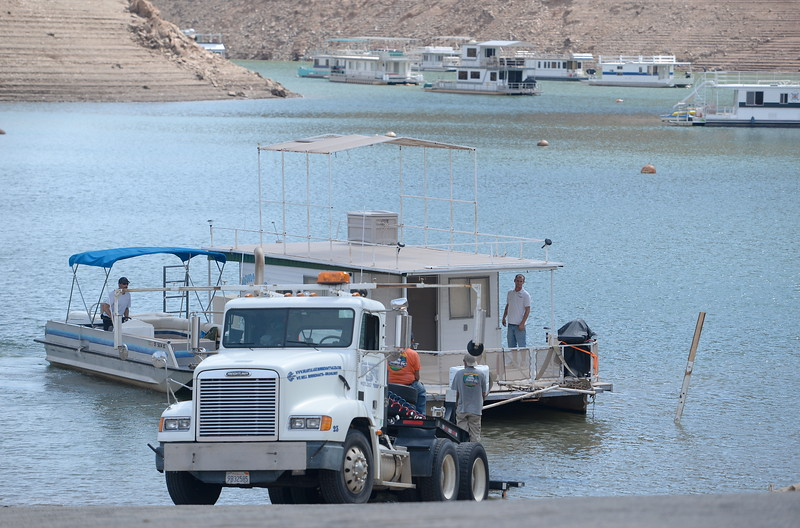 Forever Resorts employees help bring a boat to a waiting truck as houseboats are pulled from Lake Oroville at Forever Resorts Lime Saddle Marina Monday Sept. 18, 2017. (Bill Husa -- Enterprise-Record)