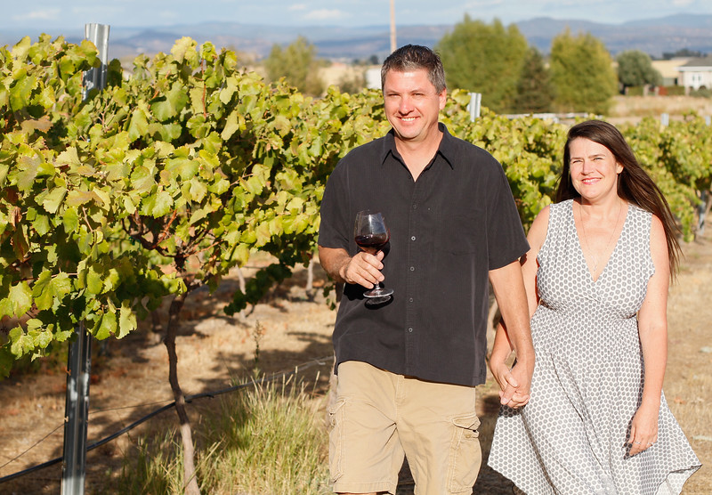 Susan and Shawn Smith take a stroll through their grape vines at Live Vine Wines September 22, 2017 in Oroville, California. (Emily Bertolino -- Mercury Register)