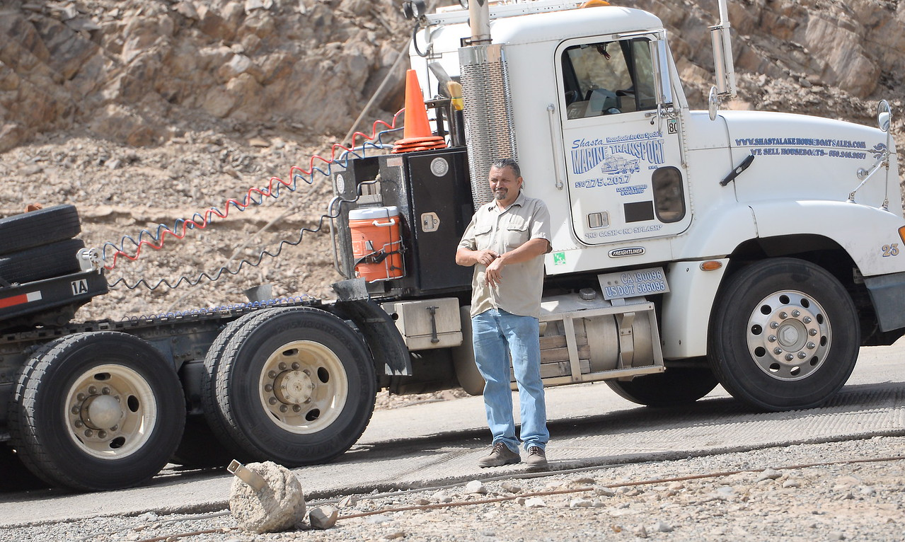 A man stands beside a houseboat moving truck as houseboats are pulled from Lake Oroville at Forever Resorts Lime Saddle Marina Monday Sept. 18, 2017. (Bill Husa -- Enterprise-Record)