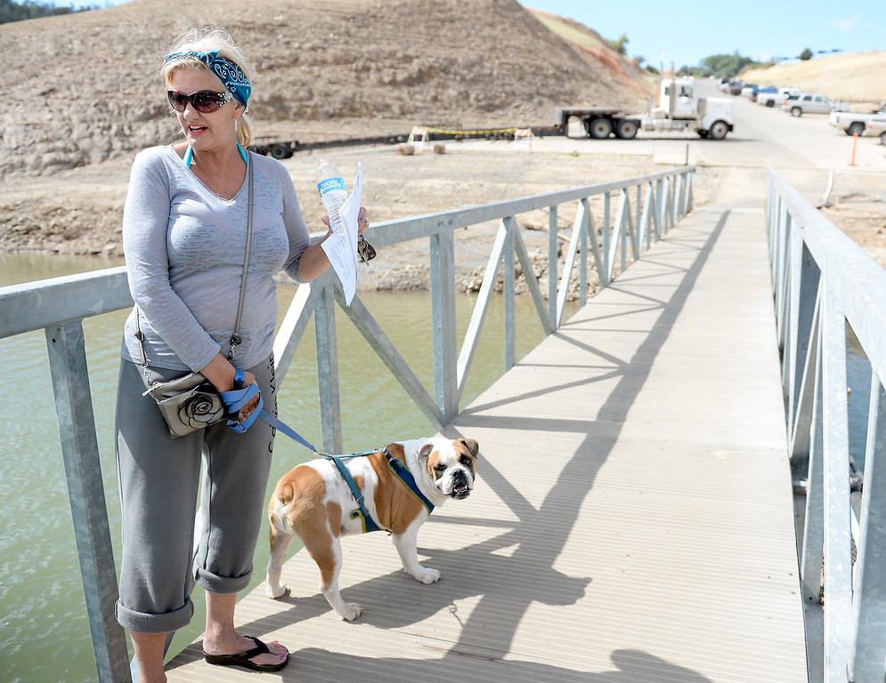 . Susan Soto-Henderson of Oroville talks about some of the fees and frustrations of being a boat owner as she and her dog Cooper Riley walk along the dock at Lake Oroville at Forever Resorts Lime Saddle Marina Monday Sept. 18, 2017. (Bill Husa -- Enterprise-Record)