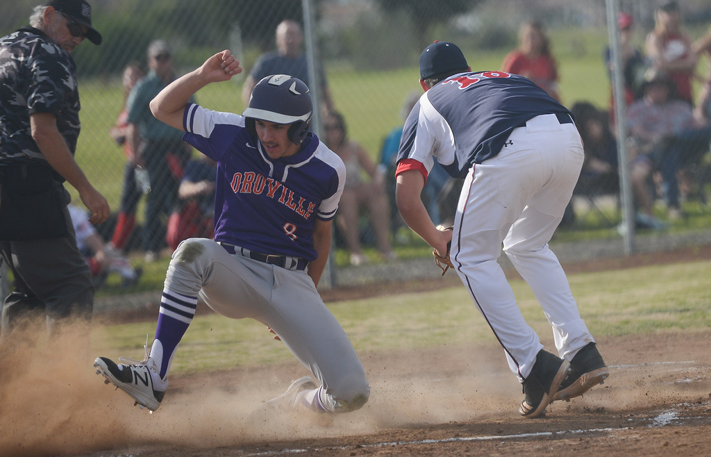 . Oroville High\'s Colton Rogers slides to home base, narrowly missing Las Plumas High\'s Mason Whitfield, March 29, 2018, in Oroville, California. (Carin Dorghalli -- Enterprise-Record)