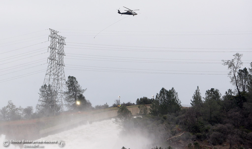 . Several helicopters are busy with repairs while a bit under 100,000 cfs flows down the damaged spillway as the Lake Oroville Dam Spillway emergency continues in Oroville, Calif. Wed. Feb. 15, 2017. (Bill Husa -- Enterprise-Record)