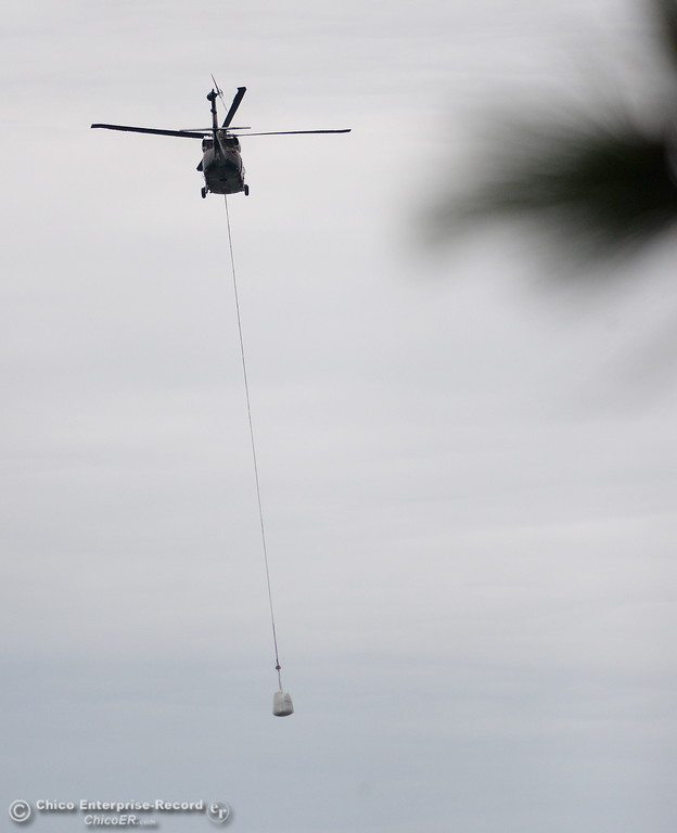 . A helicopter flys with a bag full of rocks as the Lake Oroville Dam Spillway emergency continues in Oroville, Calif. Wed. Feb. 15, 2017. (Bill Husa -- Enterprise-Record)
