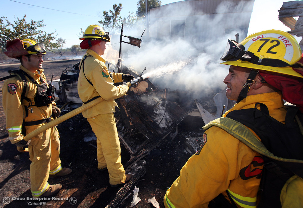 . Cal Fire - Butte County firefighters Brad Padilla, Ibe Liebenberg, and Mike Lamonica (left to right) battle a fire burning a trailer off Vineyard Lane Friday, July 12, 2013 in Oroville, Calif.  (Jason Halley/Chico Enterprise-Record)