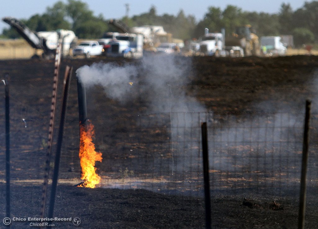 . A fence post burns as Cal Fire - Butte County firefighters battle a fire off Vineyard Lane Friday, July 12, 2013 in Oroville, Calif.  (Jason Halley/Chico Enterprise-Record)