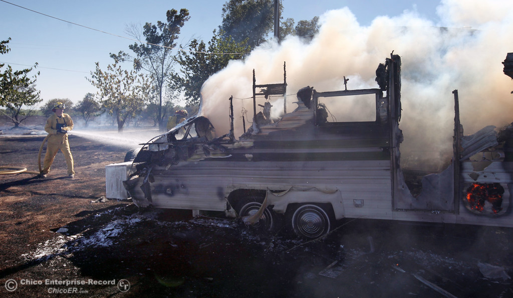 . Cal Fire - Butte County firefighters Ibe Liebenberg (left) battles a fire burning a trailer off Vineyard Lane Friday, July 12, 2013 in Oroville, Calif.  (Jason Halley/Chico Enterprise-Record)