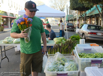 Kaleb Craig browses the produce at Fruitiya Farms' booth after purchasing a bouquet at the Oroville Downtown Business Association Farmers Market on Wednesday, March 30, 2016, on  Myers Street in Oroville, California. (Dan Reidel -- Mercury-Register)