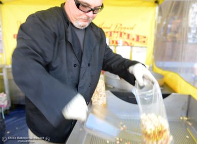 Adam Baker, of Baker's Choice Kettle Corn fills a bag full of the sweet popped corn during the Historic Downtown Oroville Certified Farmers Market on Wednesday, March 30, 2016, on  Myers Street in Oroville, California. (Dan Reidel -- Mercury-Register)