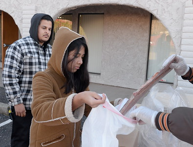 Father and daughter Manuel and Angelina Ramirez are some of the more than 130 people lined up to receive some of the 10,000 lbs. of salmon fillets being handed out during the Salmon giveaway at the Enterprise Rancheria in Oroville, Calif. Thurs. Dec. 29, 2016. (Bill Husa -- Enterprise-Record)