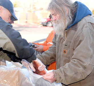 At right Mike Verzani picks up salmon fillets being handed out during the Salmon giveaway at the Enterprise Rancheria in Oroville, Calif. Thurs. Dec. 29, 2016. Verzani said his plan is to smoke his fish. (Bill Husa -- Enterprise-Record)
