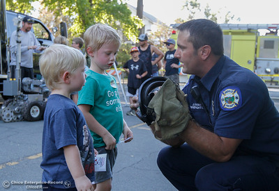Oroville firefighter Justin Khan explains to Hunter Mendenhall, 2, and Cameron Mendenhall, 4, that firefighters wear masks and not to be afraid if a firefighter comes into their house during a fire with the mask on, that they are there to help as he shows the two around the fire truck at the annual National Night Out August 2, 2016 at the Lott Home in Oroville, Calif. (Emily Bertolino -- Mercury Register)