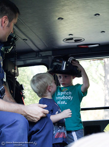 Cameron Mendenhall, 4, tries on firefighter helmet and shows his brother Hunter, 2, as Firefighter Khan gives the two a tour of an Oroville fire engine at the annual National Night Out August 2, 2016 at the Lott Home in Oroville, Calif. (Emily Bertolino -- Mercury Register)