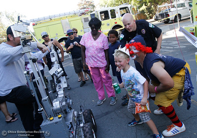 BackDraft Buddy sneaks up behind RJ Newens, 7, as Newens looks at himself in the monitor that's streaming from the Butte County Inter-Agency Bomb Squad's robot at the annual National Night Out  August 2, 2016 at the Lott Home in Oroville, Calif. (Emily Bertolino -- Mercury Register)