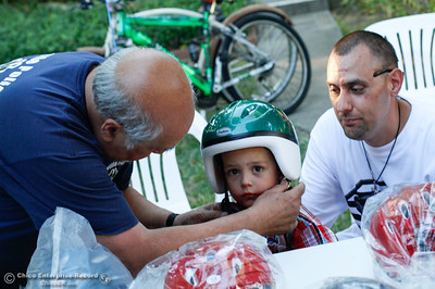 Oroville Police Department VIP Del Rosario helps Anthony Zavala, 3, fit a new helmet he received after winning a new bike in the VIP raffle as his dad Erik looks on at the annual National Night Out August 2, 2016 at the Lott Home in Oroville, Calif. (Emily Bertolino -- Mercury Register)