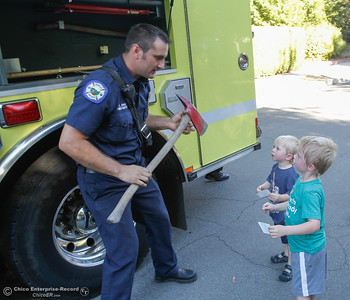 Oroville firefighter Justin Khan asks Hunter Mendenhall, 2, and Cameron Mendenhall, 4, what the object is in his hand as he shows the two around the fire truck at the annual National Night Out August 2, 2016 at the Lott Home in Oroville, Calif. (Emily Bertolino -- Mercury Register)