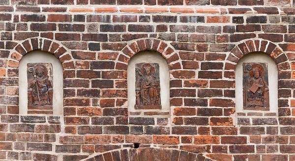 Jerichow, Stiftskirche: Terrakottareliefs über Westportal (Hl. Nikolaus, Maria, hl. Augustinus ?)