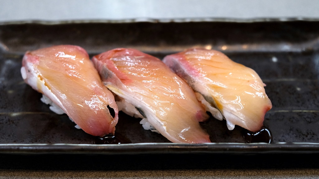 3 pieces of hamachi nigiri brushed with soy sauce.