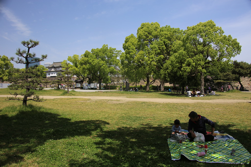 A family relaxes in the shade of Osaka Castle Park
