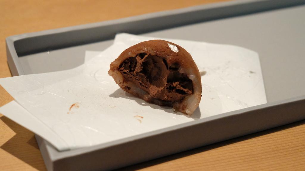 A half-bitten dark chocolate daifuku mochi.