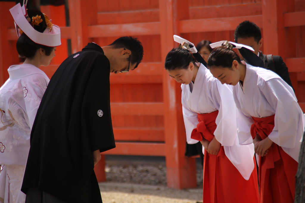 A wedding couple bow to the shrine attendants before the procession begins